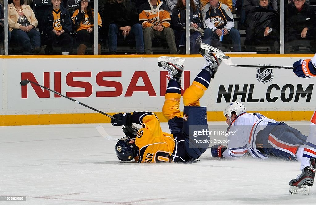 Bobby Butler #19 of the Nashville Predators gets tripped by <a gi-track='captionPersonalityLinkClicked' href=/galleries/search?phrase=Ryan+Whitney&family=editorial&specificpeople=584338 ng-click='$event.stopPropagation()'>Ryan Whitney</a> #6 of the Edmonton Oilers at Bridgestone Arena on March 8, 2013 in Nashville, Tennessee.