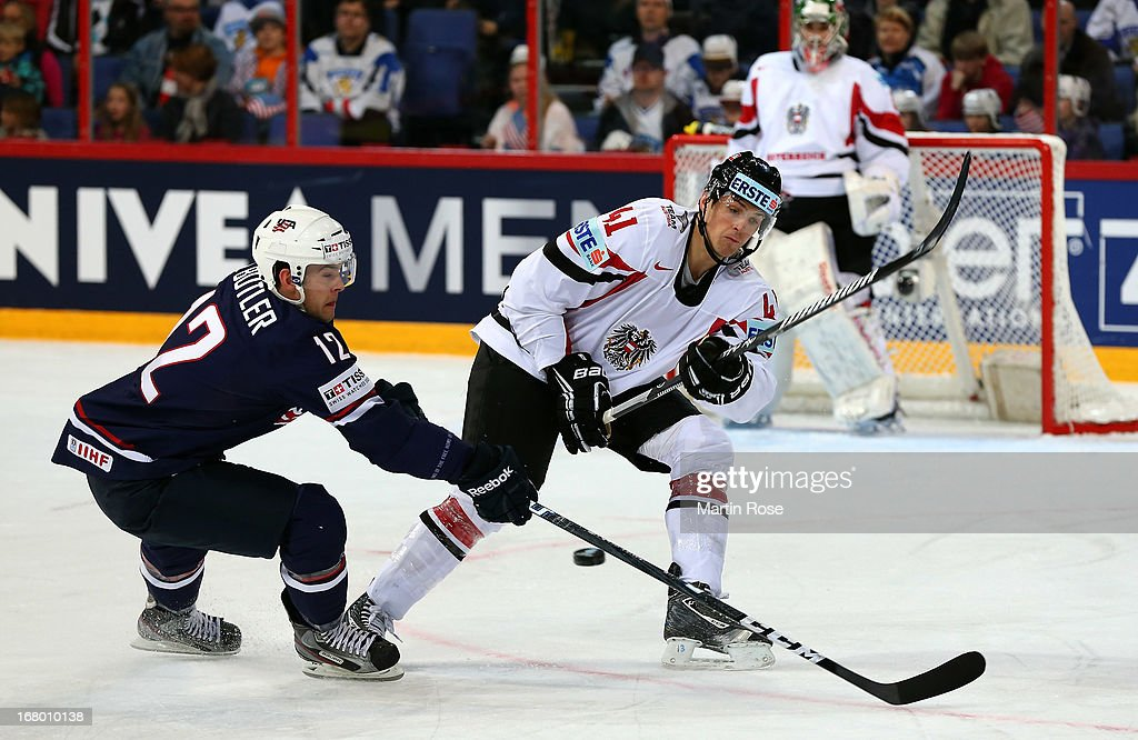 Bobby Butler of USA and Mario Altmann of Austria battle for the puck during the IIHF World Championship group H match between USA and Austria at...
