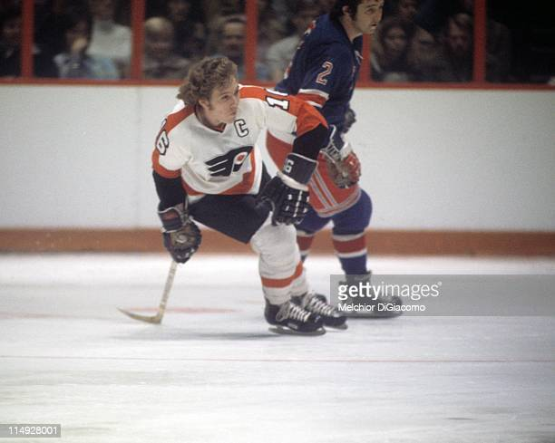 Bobby Clarke of the Philadelphia Flyers and Brad Park of the New York Rangers skate on the ice during an NHL game circa 1975 at the Spectrum in...