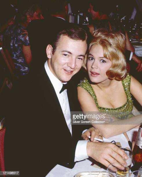 Bobby Darin US actor and singer wearing a black dinner suit with a white shirt and a black bow tie sitting beside his wife Sandra Dee US actress...