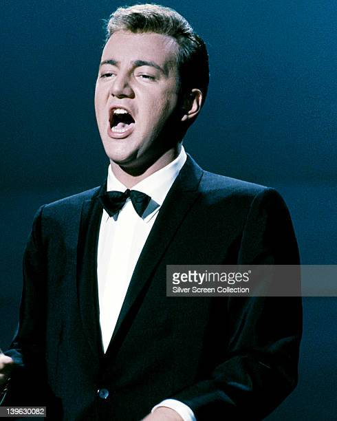 Bobby Darin US singer and actor singing while wearing a black tuxedo with a white shirt and a black bow tie against a dark blue background circa 1965