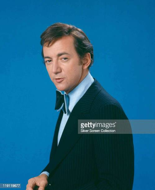 Bobby Darin US singer and actor wearing a dark blue pinstriped jacket a light blue shirt and dark blue bowtie in a studio portrait against a blue...