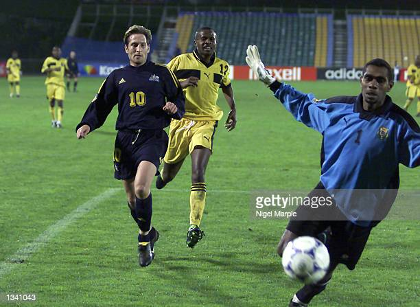 Bobby Despotovski of Australia chases down the ball with Graham Demas in pursuit watched by keeper David Chilia during the match between Australia...