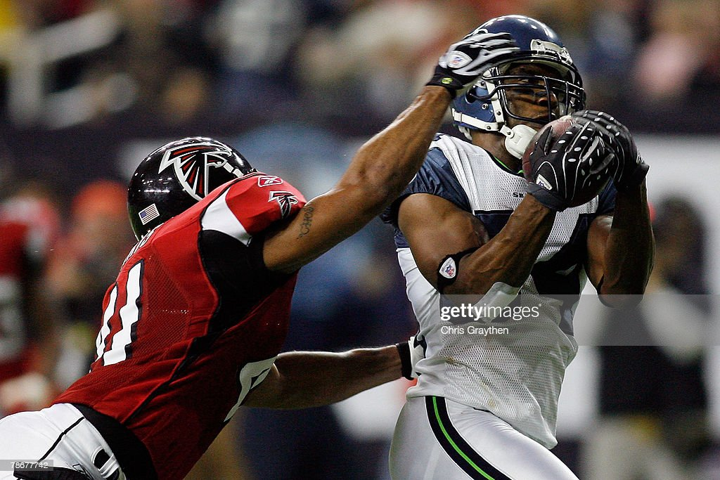 Bobby Engram #84 of the Seattle Seahawks catches a touchdown pass over Antoine Harris #41 of the Atlanta Falcons on December 30, 2007 at the Georgia Dome in Atlanta, Georgia.