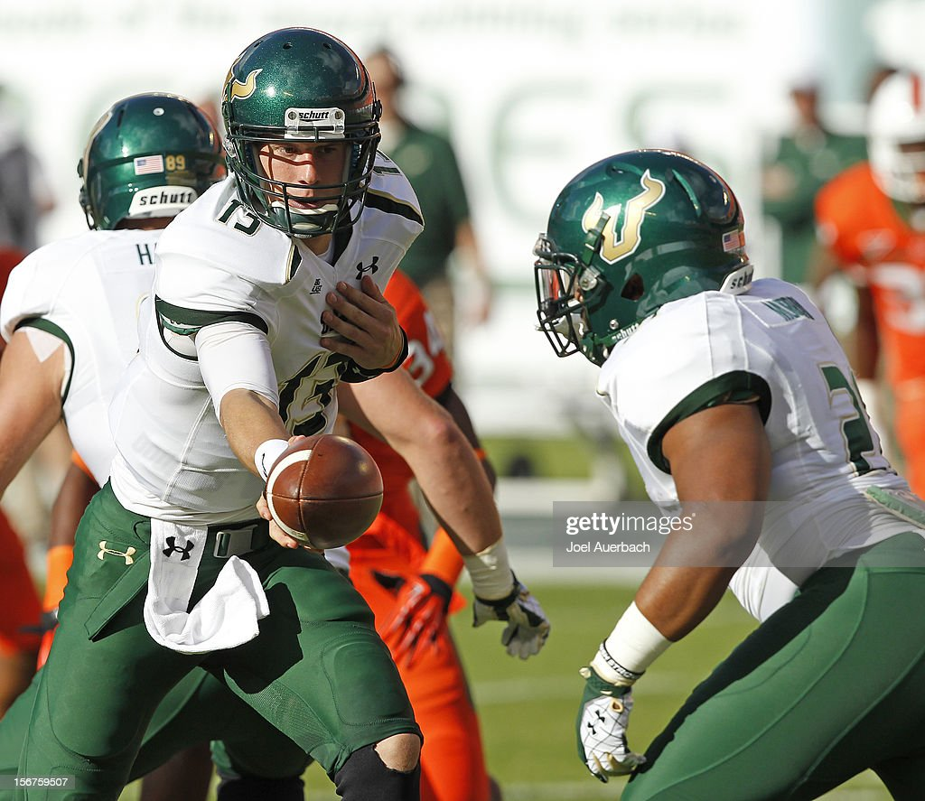 Bobby Eveld #13 of the South Florida Bulls hands the ball off to Demetris Murray #21 against the Miami Hurricanes on November 17, 2012 at Sun Life Stadium in Miami Gardens, Florida. The Hurricanes defeated the Bulls 40-9.