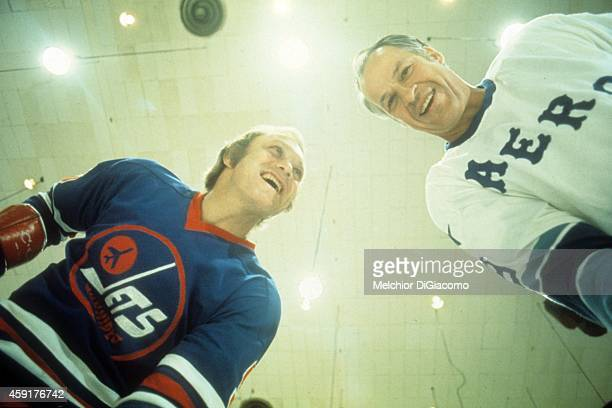 Bobby Hull of the Winnipeg Jets and Gordie Howe of the Houston Aeros faceoff over the camera during a photo shoot between the two legends before...