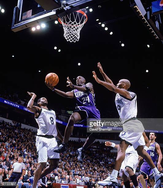 Bobby Jackson of the Sacramento Kings drives to the basket between Latrell Sprewell and Sam Cassell of the Minnesota Timberwolves during the NBA game...