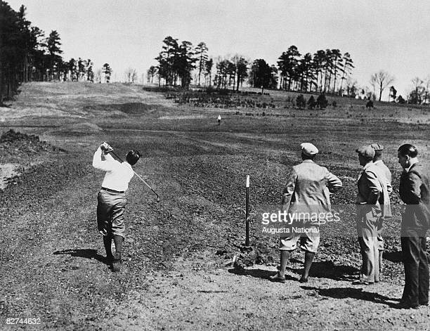 Bobby Jones plays a shot on the eighth hole while the course in under construction in front of his father Bob Jones Sr Clifford Roberts and Alister...