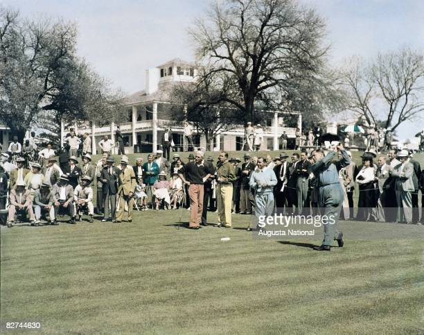 Bobby Jones plays his tee shot on the first hole while Tommy Armour Walter Hagen Gene Sarazen watch alongside a gallery of patrons in front of the...