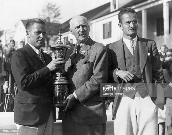 Bobby Jones receives the US amateur trophy from Findlay Douglas the President of the US Golf Association Gene Homans lost to Jones in the final by a...