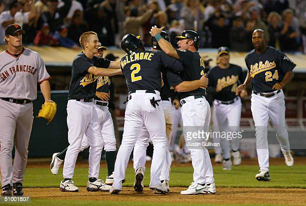 Bobby Kielty of the Oakland Athletics is surrounded by teammates after scoring the winning run during the tenth inning against the San Francisco...