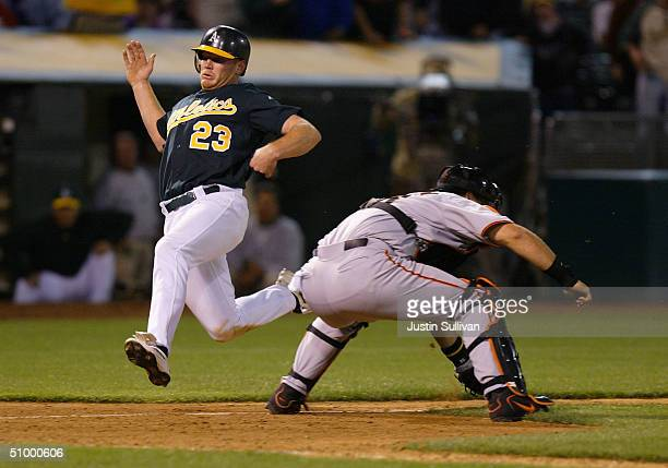 Bobby Kielty of the Oakland Athletics slides past AJ Pierzynski of the San Francisco Giants to score the winning run during the tenth inning June 26...