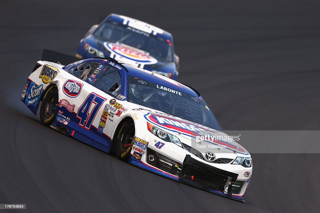 Bobby Labonte, driver of the #47 Kingsford Charcoal Toyota, spins in front of Travis Kvapil, driver of the #93 Burger King / Dr. Pepper Toyota, during the NASCAR Sprint Cup Series 44th Annual Pure Michigan 400 at Michigan International Speedway on August 18, 2013 in Brooklyn, Michigan.