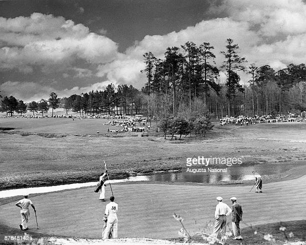 Bobby Locke of South Africa putts up the rise on the 12th green while playing Jimmy Demaret left and Sam Snead during the 1948 Masters Tournament at...