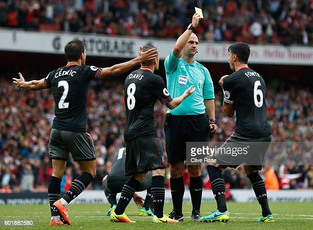 Bobby Madley gives Jose Fonte of Southampton a yellow card for a foul in the box during the Premier League match between Arsenal and Southampton at...