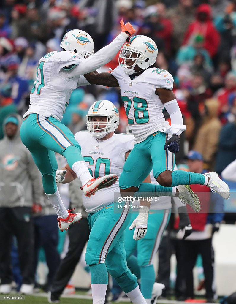 Bobby McCain #28 of the Miami Dolphins and Michael Thomas #31 of the Miami Dolphins celebrate a defensive stop on a fourth and one situation against the Buffalo Bills during the first half at New Era Stadium on December 24, 2016 in Orchard Park, New York.