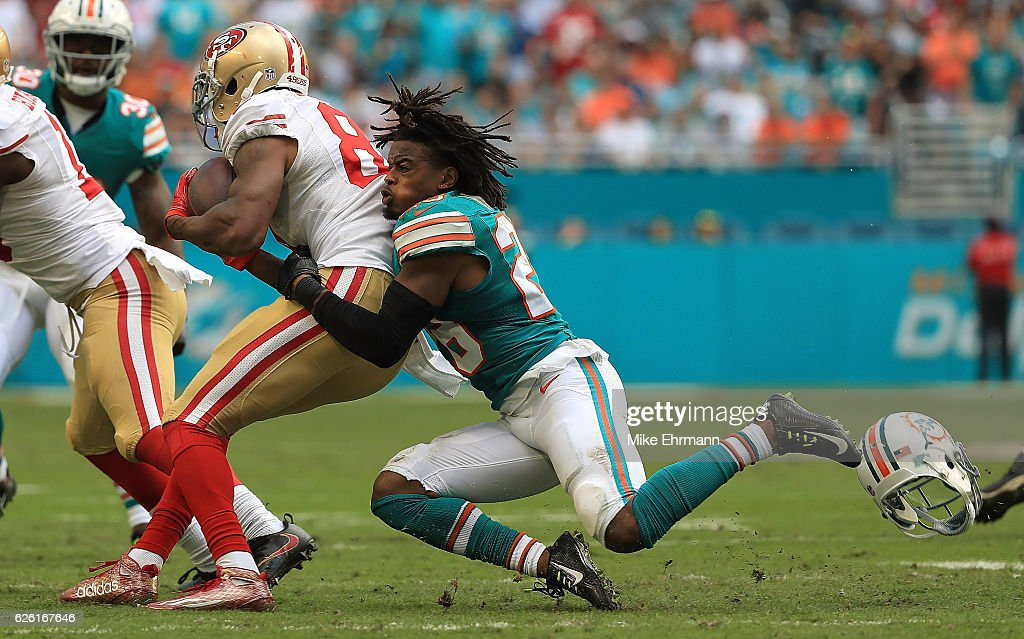 Bobby McCain #28 of the Miami Dolphins tackles Rod Streater #81 of the San Francisco 49ers during a game on November 27, 2016 in Miami Gardens, Florida.