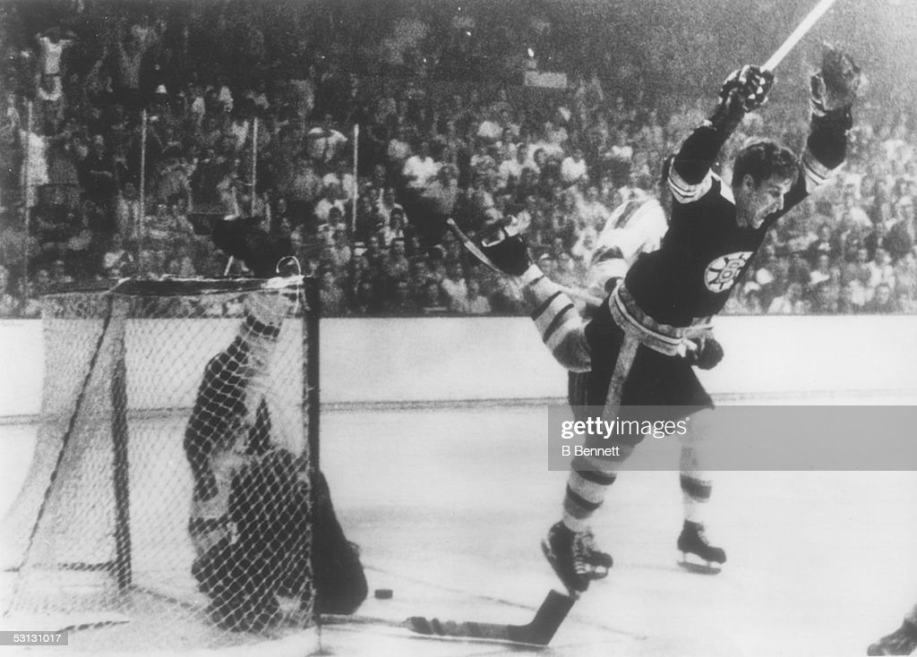 Bobby Orr of the Boston Bruins flies through the air after sliding the puck past goalie Glenn Hall and tripped by Noel Picard of the St Louis Blues...