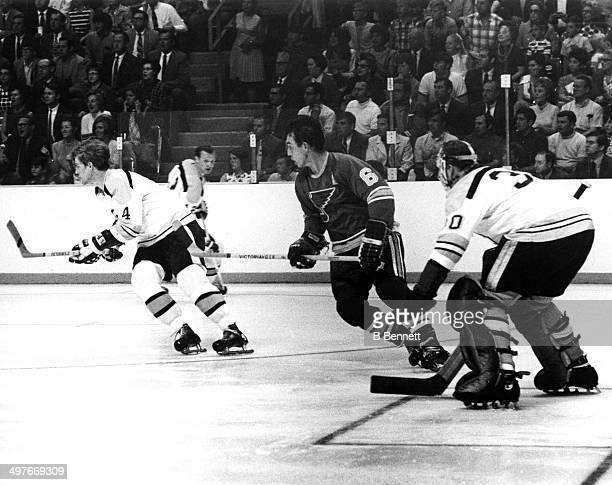 Bobby Orr of the Boston Bruins skates on the ice as he is followed by Jim Roberts of the St Louis Blues as goalie Gerry Cheevers looks on during Game...