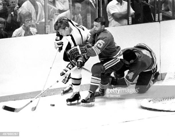 Bobby Orr of the Boston Bruins skates with the puck as he is defended by Bill McCreary and Noel Picard of the St Louis Blues during Game 1 of the...