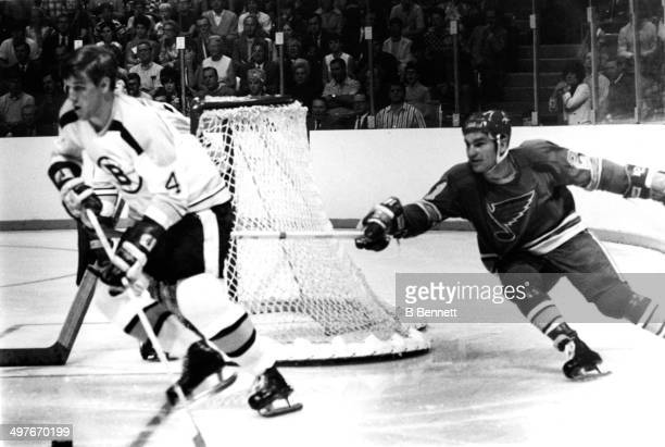 Bobby Orr of the Boston Bruins skates with the puck as he is followed by Camille Henry of the St Louis Blues during Game 2 of the 1970 Stanley Cup...