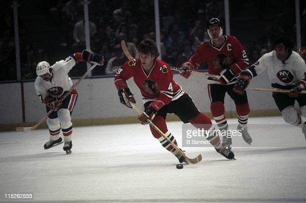 Bobby Orr of the Chicago Blackhawks skates with the puck as Jude Drouin and JP Parise of the New York Islanders follow behind along with Stan Mikita...