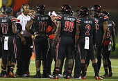 Bobby Petrino the head coach of the Louisville Cardinals gives instructions to his team during the game against the Miami Huricanesat Papa John's...