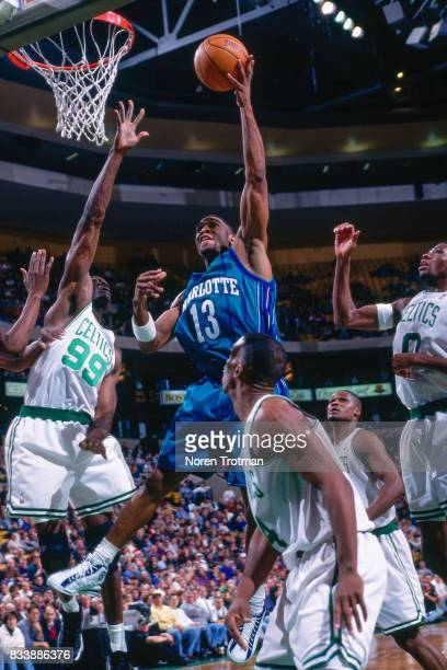 Bobby Phills of the Charlotte Hornets shoots the ball between defenders against the Boston Celtics at the Boston Garden in Boston Massachusetts circa...