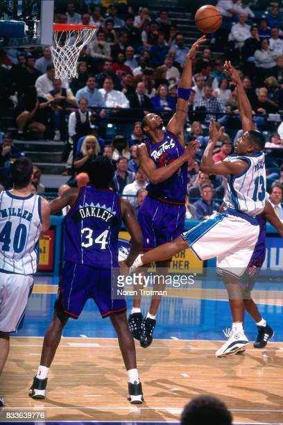 Bobby Phills of the Charlotte Hornets shoots the ball over Tracy McGrady of the Toronto Raptors at the Charlotte Coliseum in Charlotte North Carolina...