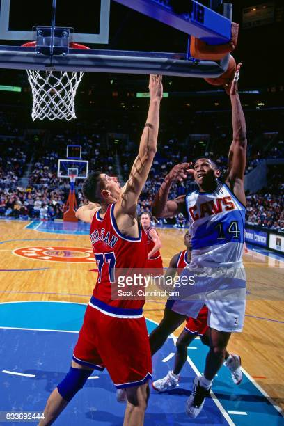 Bobby Phills of the Cleveland Cavaliers drives to the basket and shoots the ball over Gheorghe Muresan of the Washington Bullets at Gund Arena in...