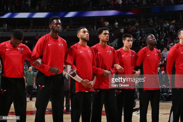 Bobby Portis and Denzel Valentine of the Chicago Bulls with their teammates stand for the National Anthem before the preseason game against the...