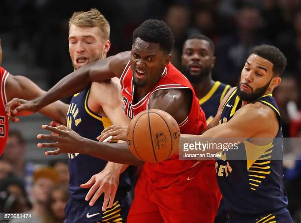 Bobby Portis of the Chicago Bulls battles for a loose ball with Domantas Sabonis and Cory Joseph of the Indiana Pacers at the United Center on...