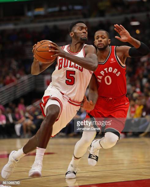 Bobby Portis of the Chicago Bulls drives past CJ Miles of the Toronto Raptors during a preseason game at the United Center on October 13 2017 in...