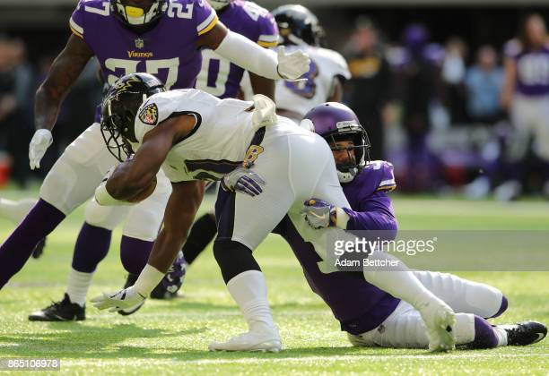 Bobby Rainey of the Baltimore Ravens is tackled by defender Marcus Sherels of the Minnesota Vikings in the second quarter of the game on October 22...
