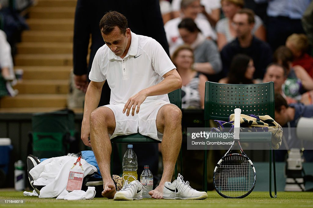 Bobby Reynolds of the United States of America takes his shoes off during a break in his Gentlemen's Singles second round match against Novak Djokovic of Serbia on day four of the Wimbledon Lawn Tennis Championships at the All England Lawn Tennis and Croquet Club on June 27, 2013 in London, England.