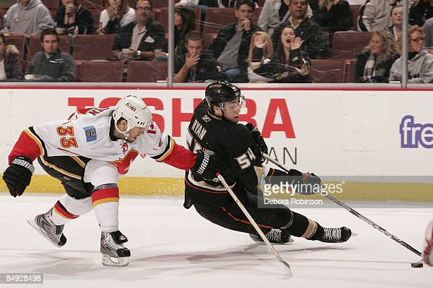 Bobby Ryan of the Calgary Flames controls the puck against Adrian Aucoin of the Anaheim Ducks during the game on February 11 2009 at Honda Center in...