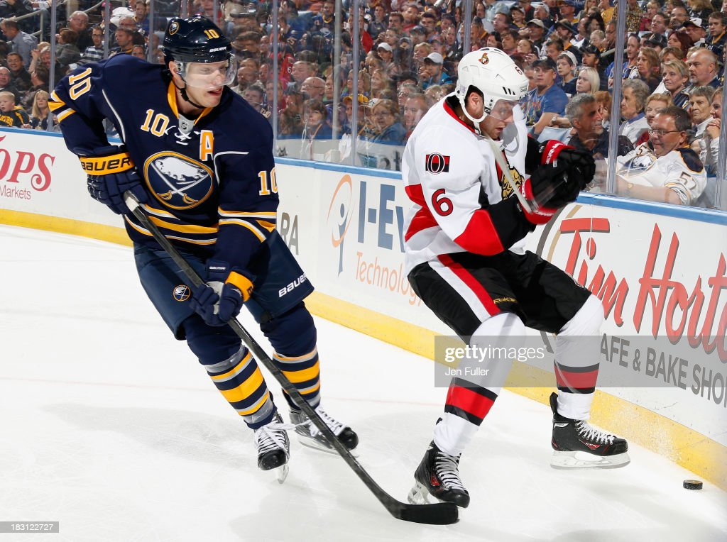 Bobby Ryan #6 of the Ottawa Senators and Christian Ehrhoff #10 of the Buffalo Sabres battle for the puck along the boards at First Niagara Center on October 4, 2013 in Buffalo, New York.