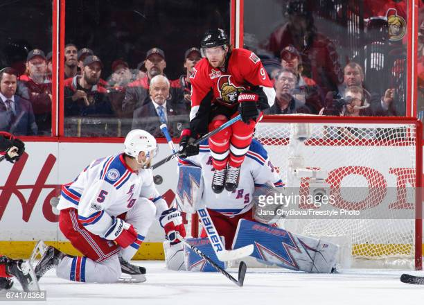 Bobby Ryan of the Ottawa Senators jumps as the puck is shot and Henrik Lundqvist of the New York Rangers makes a save and Dan Girardi of the New York...