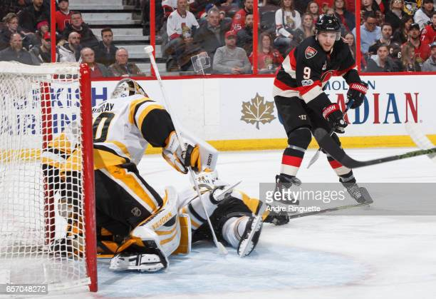 Bobby Ryan of the Ottawa Senators shoots the puck on his back hand as Matt Murray and Ian Cole of the Pittsburgh Penguins guard their net at Canadian...