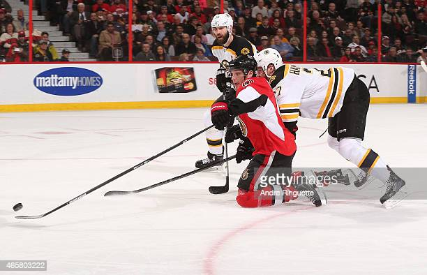 Bobby Ryan of the Ottawa Senators shovels the puck towards the net as he fights off pressure from Dougie Hamilton and Zdeno Chara of the Boston...