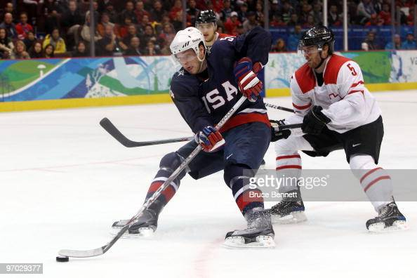 Bobby Ryan of the United States handles the puck against Severin Blindenbacher of Switzerland during the ice hockey men's quarter final game between...