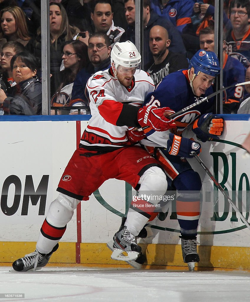 Bobby Sanguinetti of the Carolina Hurricanes holds Marty Reasoner of the New York Islanders against the boards at the Nassau Veterans Memorial...