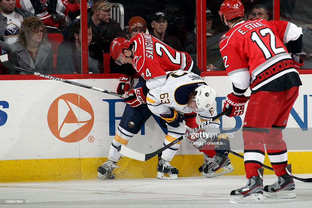 Bobby Sanguinetti #24 of the Carolina Hurricanes is checked by Tyler Ennis #63 of the Buffalo Sabres as Eric Staal #12 looks on during their NHL game at PNC Arena on January 24, 2013.