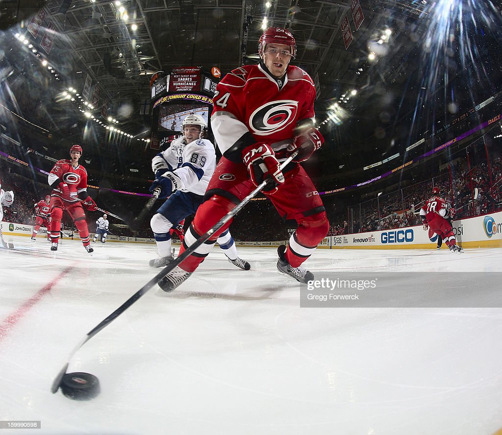 Bobby Sanguinetti #24 of the Carolina Hurricanes plays a loose puck along the boards away from Cory Conacher #89 of the Tampa Bay Lightning during their NHL game at PNC Arena on January 22, 2013 in Raleigh, North Carolina.