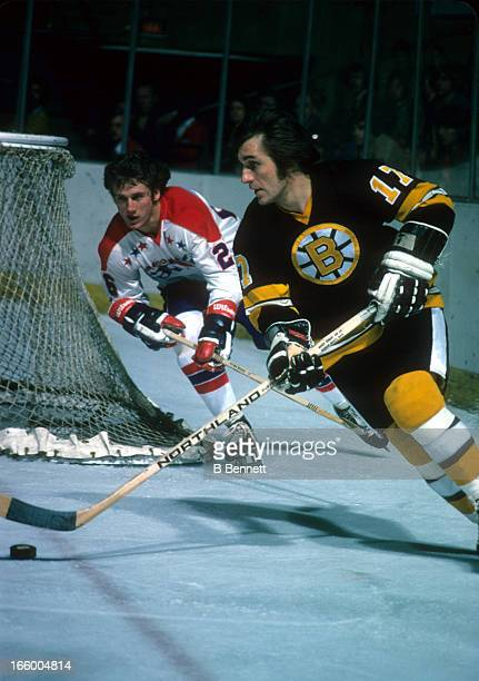 Bobby Schmautz of the Boston Bruins skates with the puck as Nelson Pyatt of the Washington Capitals defends on March 4 1975 at the Capital Centre in...
