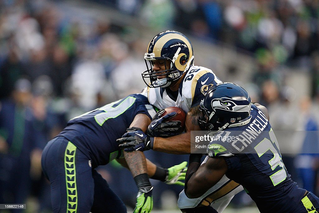 Bobby Wagner (L) #54 and Kam Chancellor (R) #31 of the Seattle Seahawks tackle Lance Kendricks #88 of the St. Louis Rams at CenturyLink Field on December 30, 2012 in Seattle, Washington.