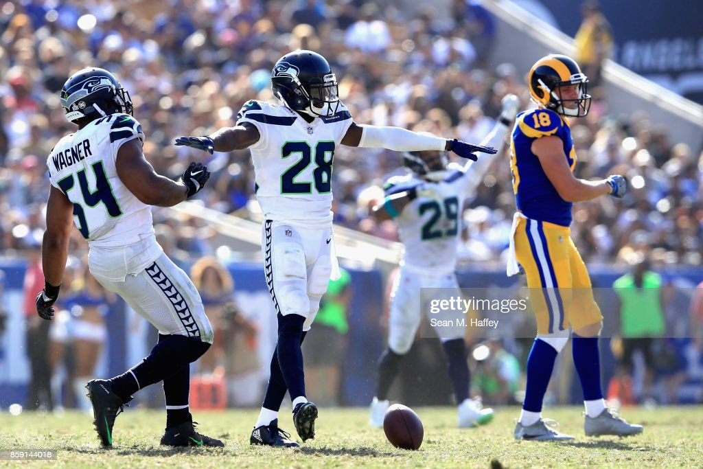 Bobby Wagner #54, Justin Coleman #28 and Earl Thomas #29 of the Seattle Seahawks react to breaking up a pass play to Cooper Kupp #18 of the Los Angeles Rams during the second half of a game at Los Angeles Memorial Coliseum on October 8, 2017 in Los Angeles, California.