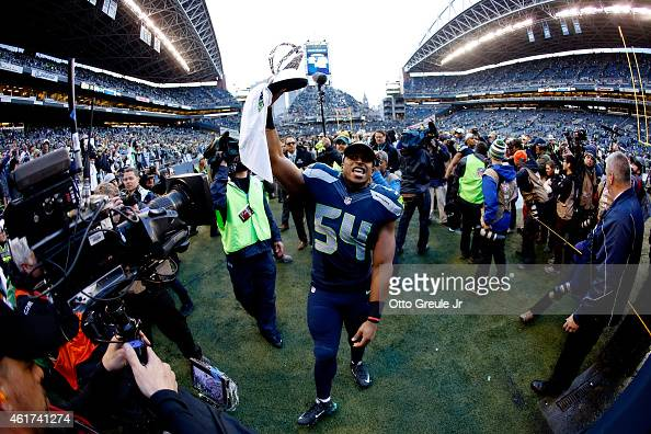 Bobby Wagner of the Seattle Seahawks holds up the George S Halas trophy as he walks off the field after the Seahawks defeated the Green Bay Packers...
