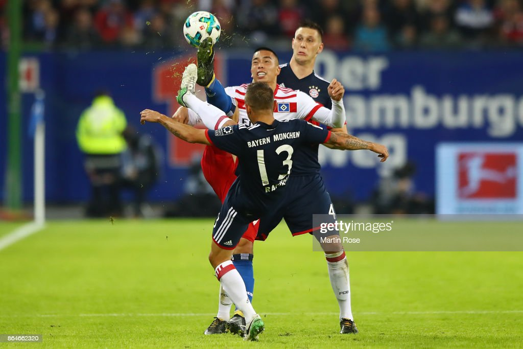 Bobby Wood of Hamburg (c) is challenged by Rafinha of Bayern Muenchen (front) and Niklas Suele of Bayern Muenchen during the Bundesliga match between Hamburger SV and FC Bayern Muenchen at Volksparkstadion on October 21, 2017 in Hamburg, Germany.