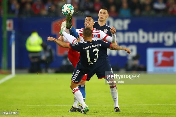 Bobby Wood of Hamburg is challenged by Rafinha of Bayern Muenchen and Niklas Suele of Bayern Muenchen during the Bundesliga match between Hamburger...